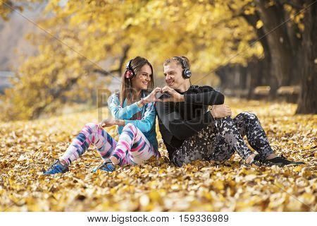 Beautiful Young Couple Resting And Listening Music After Successful Training In The Park. Hand Shape