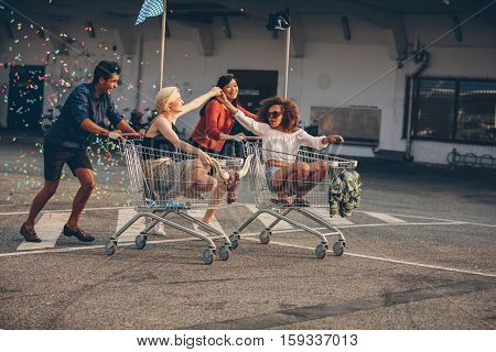 Young friends having fun on shopping carts. Multiracial young people racing on shopping cart.
