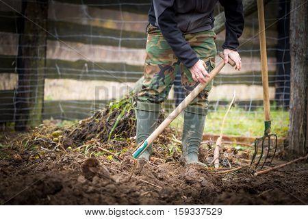 Man digging with spade in autumn or spring garden
