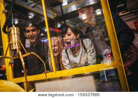 Excited Young Friends Playing Toy Grabbing Game