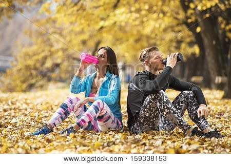 Beautiful Young Couple Resting And Rehydration After Successful Training In The Park. Autumn Environ