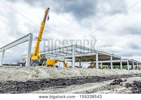 Mobile crane is finished his work to assembly huge concrete hall.