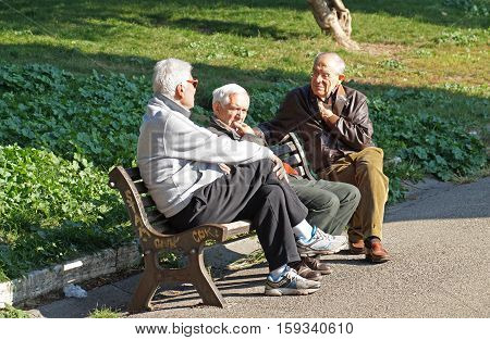 ROME , ITALY - 20 NOVEMBER 2015 : Conversation. Three old men conversing sitting on a bench in the park on a sunny day in the city of Rome. The park has always been a place of common aggregation