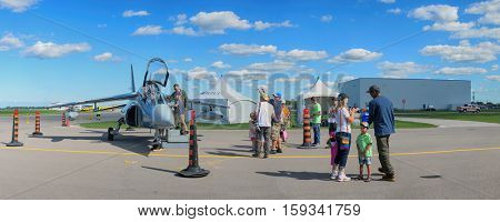 WINDSOR, CANADA - SEPT 10, 2016:  Panoramic view of canadian military Jet Trainer and pilot iand audience at the Windsor Aviation Museum air show exhibit.