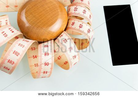 Yo-yo effect in diet concept. Wooden yoyo with centimeter measure. Bathroom weight scale with black screen display.