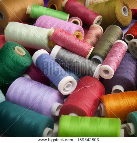 Snapshot of the pile of colorful spools of thread. Sewing conceptual background.