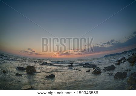 Sunset over the coast with stones of Black Sea Russia. Fish-eye lens.