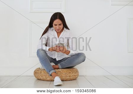 Nice pleasant concentrated woman sitting on a hassock and using cell phone while texting with colleagues