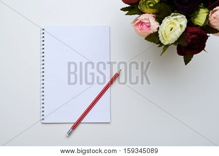 A mid shot of white jotter and a red pencil placing next to the circle of peonies. Objects against the sweet white background