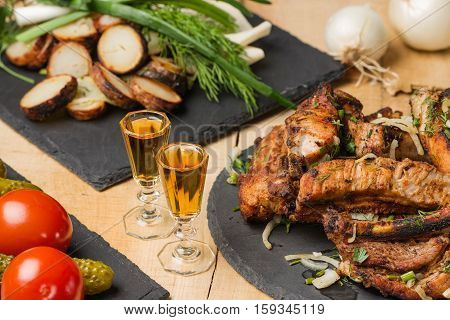 Fried meat, potatoes, greens, vegetables on slate plates and two shot glasses with cognac in style a rustic