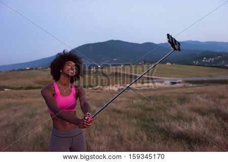 Healthy Looking Smiling Young African American Female in sports apparel photographing herself with a selfie stick beautiful summer evening in nature
