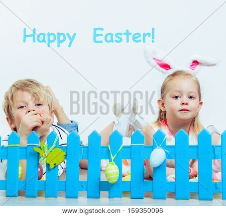 Preschool girl and boy lying behind blue fence with Easter decoration