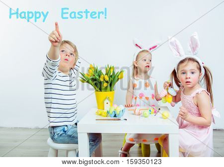 Three toddlers sitting at the table painting Easter eggs
