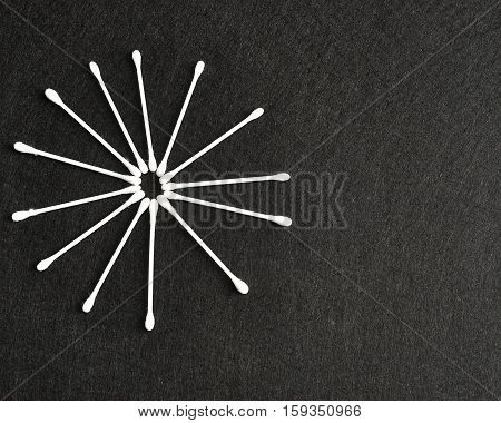Cotton swabs isolated on a light black background in a shape of a star