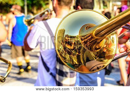 Trombone and blurry musicians playing catchy music at sunny day at Festival Fanfare Activist, Festival de Fanfarras Ativistas - HONK RiO 2016 at Leme district, Rio de Janeiro, Brazil