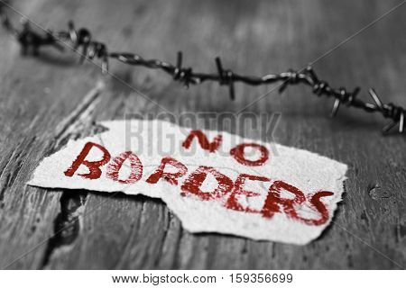 closeup of a barbed wire and a piece of paper with the text no borders handwritten in it on a rustic wooden surface