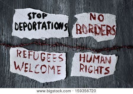 high-angle shot of a barbed wire and some pieces of paper with different messages, such as stop deportations, no borders, refugees welcome and human rights written in them, on a rustic wooden surface