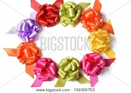some satin gift ribbon bows of different colors on a white background forming a circle, with a negative space in the center