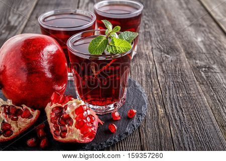 Glasses of pomegranate juice with fresh pomegranate fruits and mint on wooden table healthy drink concept.