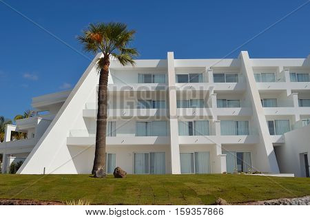 PLAYA BLANCA, LANZAROTE, SPAIN - NOVEMBER 19, 2016: Seafront White Washed  Holiday Hotel with Palm Tree Lanzarote Spain.