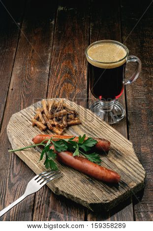 Beer With Foam And Grilled Sausages On Wood Plate