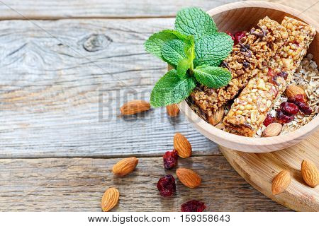 Wooden Bowl With Bars Of Cereal, Nuts, Dried Fruit And Mint.