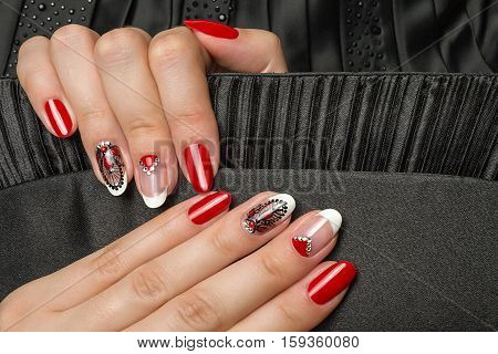 French manicure - beautiful manicured female hands with red black and white manicure with rhinestones  on black background