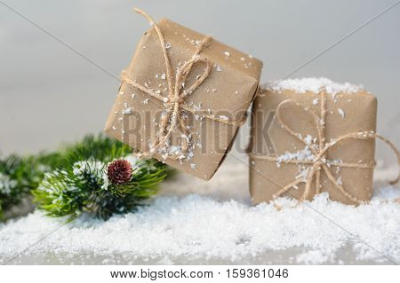 gift boxes and spruce twigs in snow. Christmas decor