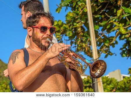 27 November, 2016. Man in sunglasses with tattoo of turtle playing trumpet in the street at sunny day at Festival de Fanfarras Ativistas - HONK RiO 2016 at Leme district, Rio de Janeiro, Brazil
