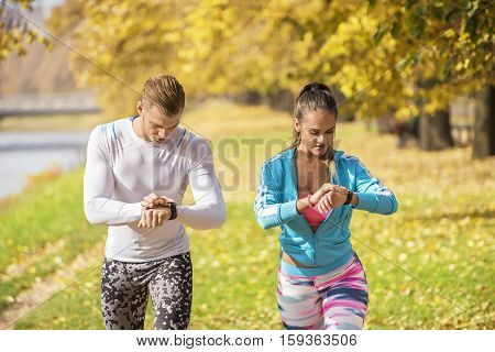 Beautiful Young Couple Preparing Their Watches For Run In The Park. Autumn Environment.