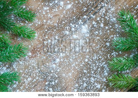 Green Christmas Tree Branches On Winter Snowflakes Wooden Space Background