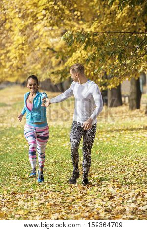 Beautiful Young Couple Running Together In The Park. Man Helps Woman Giving His Hand. Autumn Environ