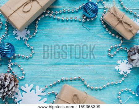 Kraft gift boxes, bead, snowflakes, Christmas decorations, cones on the wooden blue background. Shallow Selective focus. Copyspace. Shallow Selective focus. Copyspace. Top view