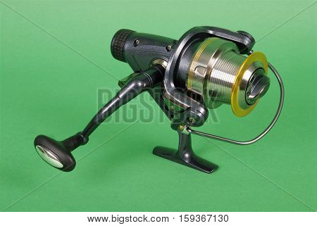 Reel for fishing rods close up on green background