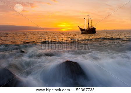 Ocean sunset ship is an old pirate ship out at sea with full flags flying as the sun sets in an orange color filled sky.