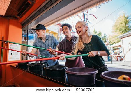 Group of friends having fun with fishing game in amusement park. Young men and woman playing arcade game.
