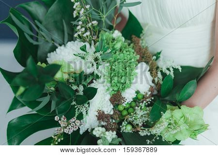 Wedding bridal bouquet with big tropical green leaves and white flowers.