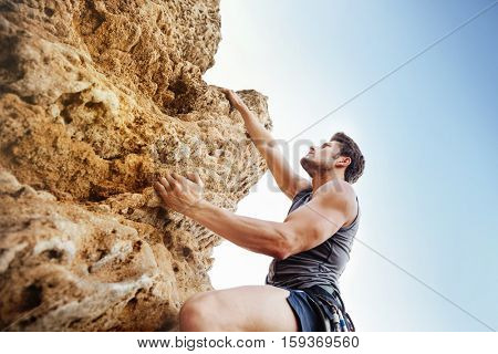 Double exposure of a man reaching for a grip while he rock climbs on a steep cliff