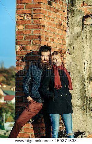 Young couple of pretty cute girl or beautiful sexy woman and handsome bearded man hipster with beard sunny outdoor on roof near red brick wall background