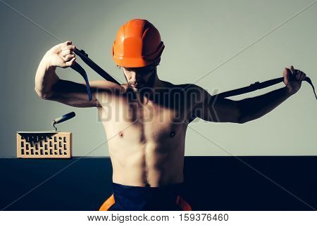 young handsome bearded macho man builder with sexy muscular athletic strong body has strong hands in blue uniform and orange hard hat or helmet undressing near brick and spatula