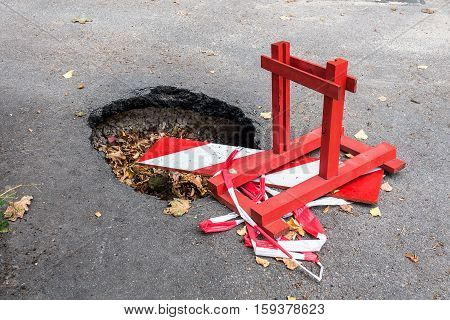 Big pothole on the road and warning sign. Road under constructon.