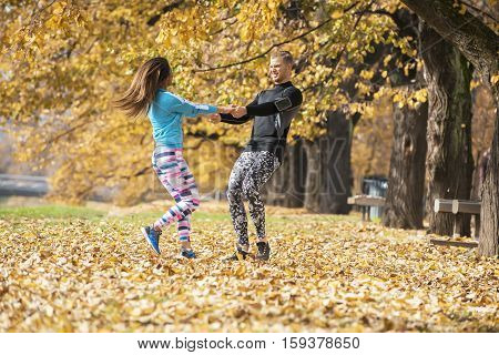 Beautiful Young Couple Enjoying And Rotating Together In The Park. Autumn Environment.