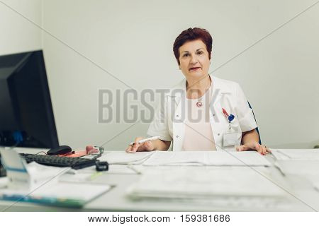 Taking care of your health concept. Experienced doctor prescribing medicines. Senior medical professional writing patients medical record. Retiring doctor.Retirement
