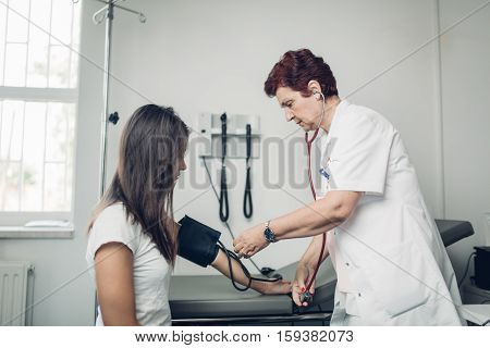 General practicioner measuring her patient's heart pressure and smiling to patient. Interacting and taking care of patient. Taking care of your health. Disease prevention.
