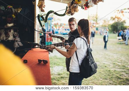 Siblings having a great time at an amusement park playing shooting game. Smiling and enjoying in sunny summer day. Siblings bonding. Spending quality time.
