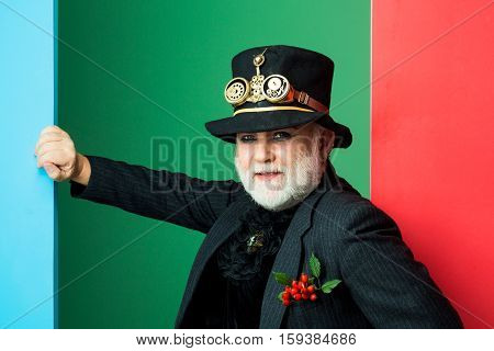 Senior bearded man or watchmaker with white beard in black hat with watch mechanical metallic gears and cogwheels on colorful wall