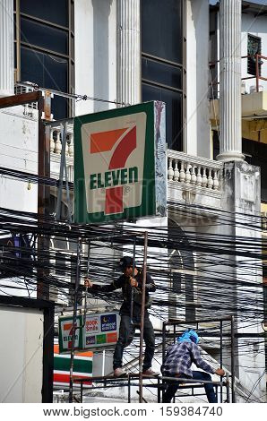 PATTAYA THAILAND - 19 NOV 2016: Electrician lineman repairman worker at climbing work on electric post power pole under 7-11 sign