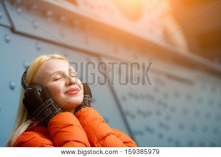 Girl in orange jacket relishing music on headphones indoors
