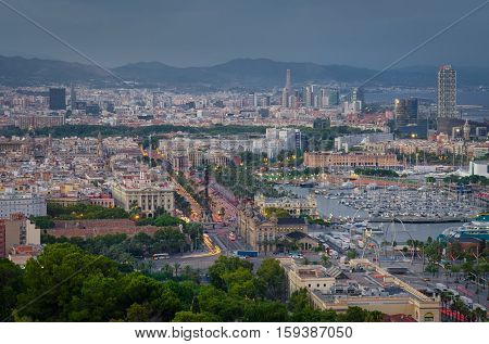 Early evening with illumination in Barcelona port and Columbus statue, summer Spain