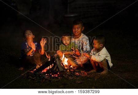 Disadvantaged children are sitting by a warm fire.